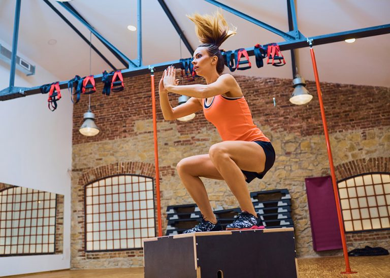 Young woman doing ox jump exercise at gym